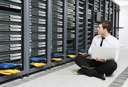 young it  engeneer business man with thin modern aluminium laptop in network server room Stock Photo - 8773884