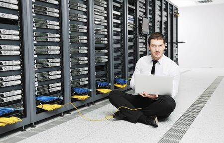 young it  engeneer business man with thin modern aluminium laptop in network server room Stock Photo - 8769442