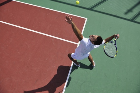 tennis serve: young man play tennis outdoor on orange tennis court at early morning Stock Photo