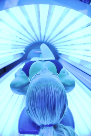 young woman at laying on solarium bed and get brown skin tone ready for summer photo