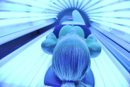 sunburned: young woman at laying on solarium bed and get brown skin tone ready for summer Stock Photo