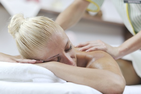 A pretty woman getting a shoulder and back massage at spa and wellness center photo