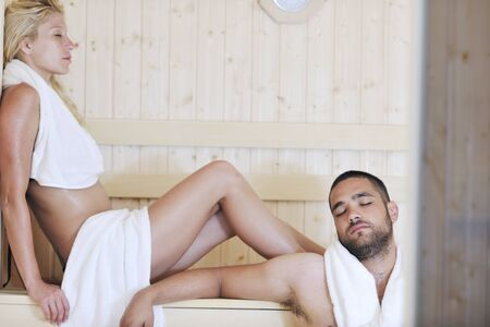 steam bath: finland sauna warming up and healing in a spa wellness resort cabin with young couple