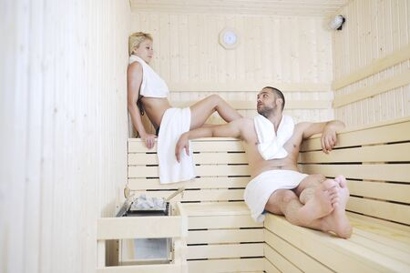 finland sauna warming up and healing in a spa wellness resort cabin with young couple photo