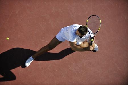 streichholz: junger Mann Tennis spielen im Freien auf orange Tennis-Feld am frühen Morgen Lizenzfreie Bilder