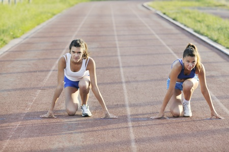 young girl morning run and competition on athletic race track photo