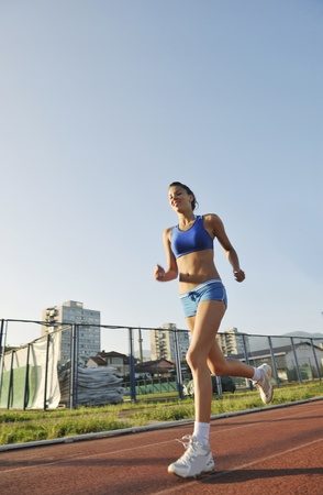 runing: beautiful young woman exercise jogging and runing on athletic track on stadium at sunrise Stock Photo