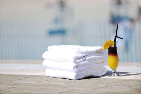coctail dring with orange att sunny day on swimming pool side with white towel decoraton Stock Photo - 8881406