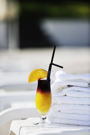 decoraton: coctail dring with orange att sunny day on swimming pool side with white towel decoraton