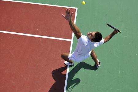 lucifers: jonge man tennissen buiten op oranje tennisbaan op vroege ochtend Stockfoto