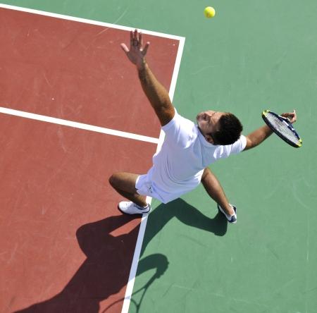 jonge man tennissen bui ten op oranje tennisbaan op vroege ochtend
