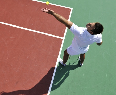 young man play tennis outdoor on orange tennis court at early morning photo