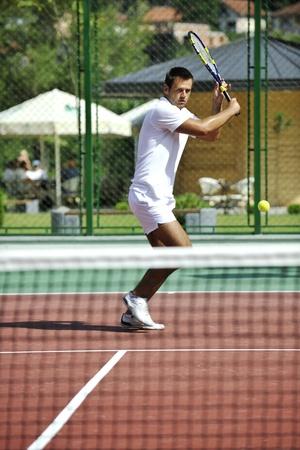 tenis: joven jugar tenis al aire libre en la cancha de tenis naranja a temprano en la ma�ana