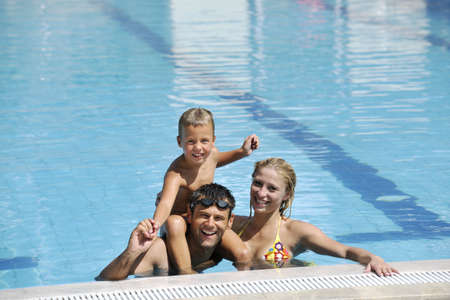 happy young family have fun on swimming pool  at summer vacation photo