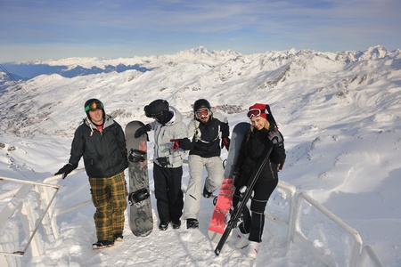 happy people group have fun on snow at winter season on mountain with blue sky and fresh air photo