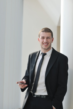 young business man talk by cellphone over bright window in big hall  photo