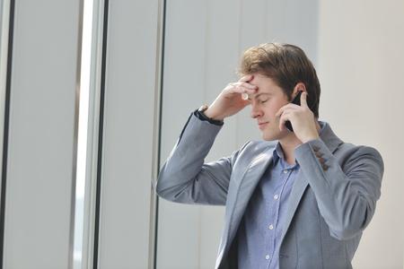 amigas conversando: hombre de negocios de j�venes hablar por celular en ventana brillante en el gran sal�n