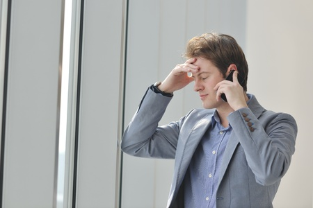 young business man talk by cellphone over bright window in big hall Stock Photo - 9076678