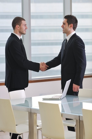 two companies: two young businessman handshake on business meeting at modern office and representing success
