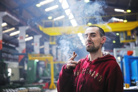 industry worker smoke cigarette at job in company at big bright hall photo
