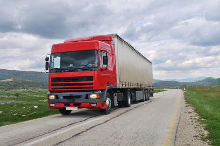 big delivery cargo  red truck on road drive fast photo