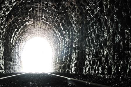 トンネル: 新しい生命との成功の概念を表す鉄道トンネルの終わりに光します。