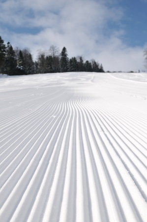 tracks on ski slopes in snow at beautiful sunny  winter day with blue sky photo