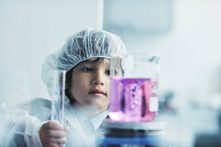 cute little male child have experiment with test tubes in bright modern lab photo