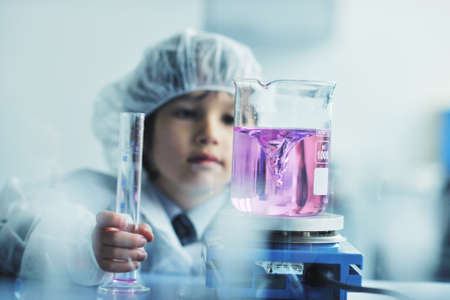 medical scientist: cute little male child have experiment with test tubes in bright modern lab