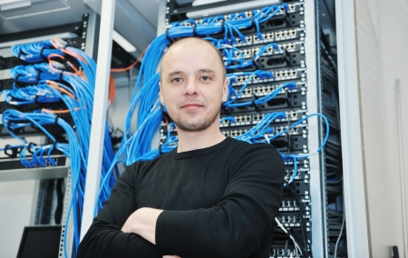 young it engineer in datacenter server room photo