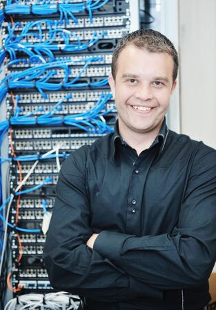 communications technology: young it engineer in datacenter server room