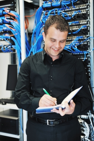 lan connection: young it engeneer in datacenter server room