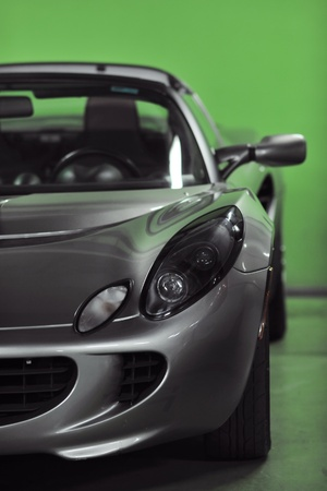 parking space: detail of sport silver car with green background