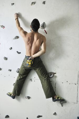 young and fit man exercise free mountain climbing on indoor practice wall Stock Photo - 9554339