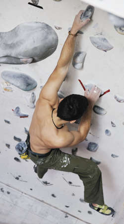 free climber: young and fit man exercise free mountain climbing on indoor practice wall