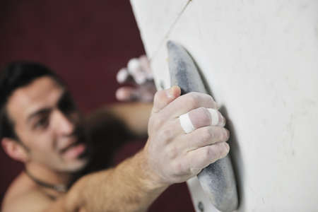 young and fit man exercise free mountain climbing on indoor practice wall Stock Photo - 9553969