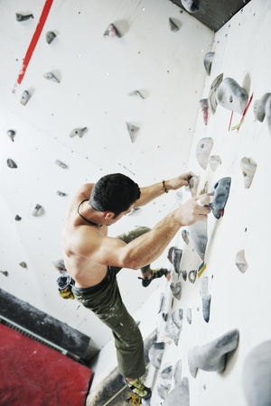 young and fit man exercise free mountain climbing on indoor practice wall Stock Photo - 9553973