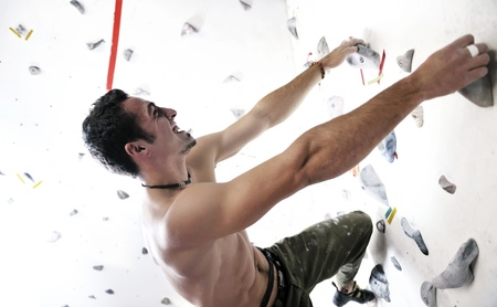 young and fit man exercise free mountain climbing on indoor practice wall Stock Photo - 9549171