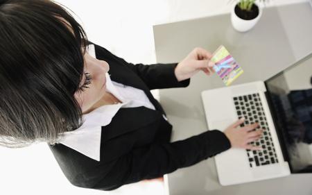 new age: joven empresaria pago en l�nea con tarjeta de cr�dito y que representa el concepto de la nueva era de dinero bancario y pl�stico