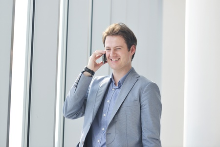 talk big: young business man talk by cellphone over bright window in big hall