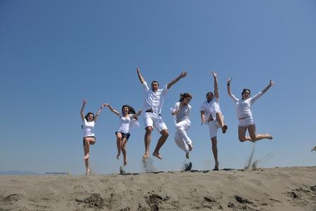 Grupo de gente feliz divertirse correr y saltar en playa hermosa playa de arena Foto de archivo