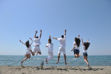 happy people group have fun  run and jump  on beach beautiful sand  beach photo