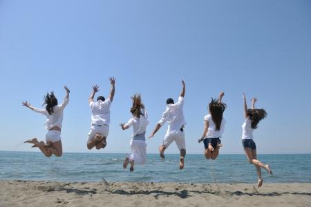 exito: Grupo de gente feliz divertirse correr y saltar en playa hermosa playa de arena