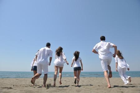 gelukkige mensen groeperen veel plezier rennen en springen op het strand prachtig zandstrand Stockfoto - 9639792