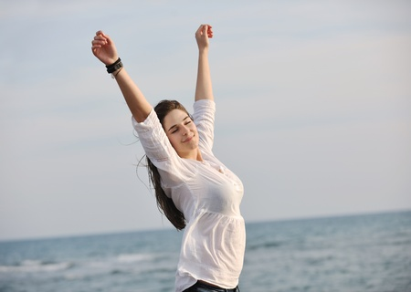 happy young woman relax on beautiful beach at fresh summer\ morning and enjoy first ray of sun
