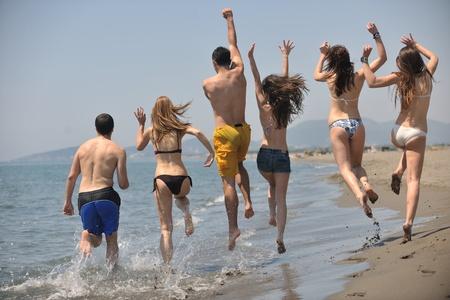 personas saltando: Grupo de gente feliz divertirse correr y saltar en playa hermosa playa de arena