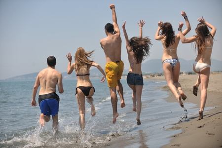 diverse people: happy people group have fun  run and jump  on beach beautiful sand  beach Stock Photo