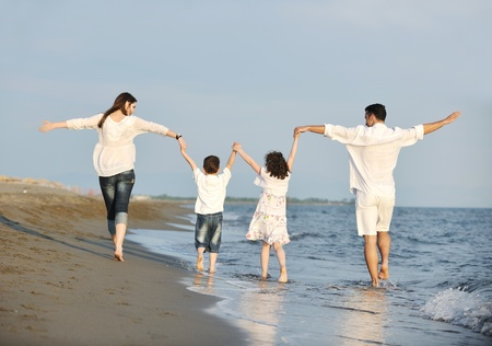 running water: happy young family have fun on beach run and jump  at sunset Stock Photo