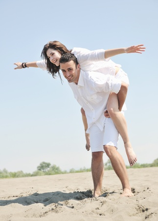 happynes: happy young couple have fun and romantic moments on beach at summer season and representing happynes and travel concept