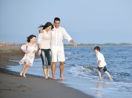 happy young family have fun on beach run and jump  at sunset Stock Photo - 9715244